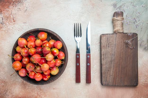 Top vue rapprochée les cerises les cerises appétissantes dans le bol le couteau fourchette planche à découper
