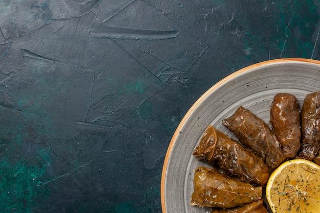 Top vue rapprochée dolma délicieux repas de viande orientale roulé à l'intérieur de feuilles vertes sur un bureau bleu foncé