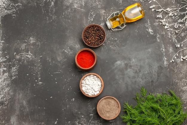 Top vue rapprochée épices bols d'herbes épices colorées bouteille d'huile