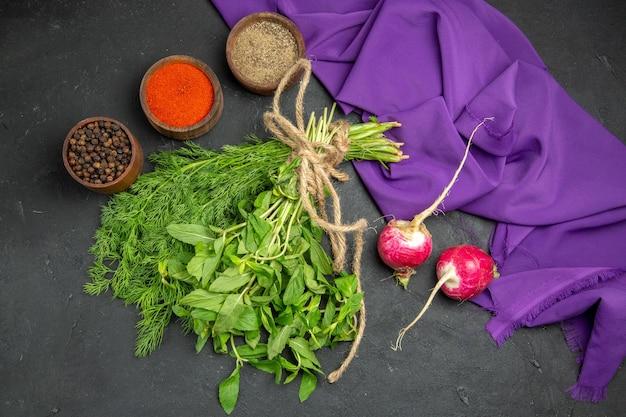 Top vue rapprochée épices trois bols d'épices radis herbes nappe violette