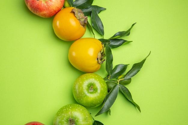 Top vue rapprochée fruits colorés pommes vertes kakis avec des feuilles sur la table