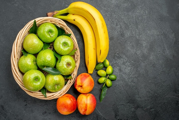 Top vue rapprochée fruits pommes dans le panier nectarines agrumes et bananes
