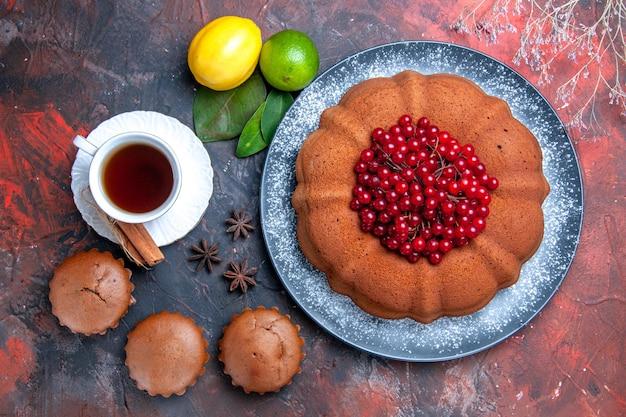 Top vue rapprochée gâteau gâteau à l'anis étoilé avec des petits gâteaux aux baies citron vert une tasse de thé