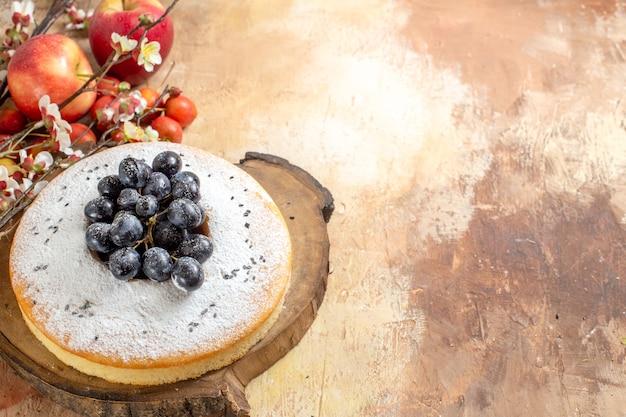 Top vue rapprochée un gâteau un gâteau appétissant avec des raisins sur le conseil des branches d'arbres de pommes cerises