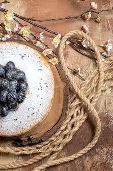 Top vue rapprochée d'un gâteau un gâteau appétissant avec des raisins noirs à côté des branches d'arbres de corde