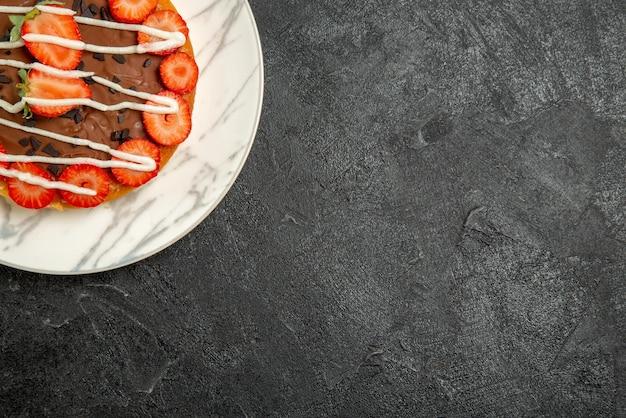 Top vue rapprochée gâteau avec plaque de chocolat de gâteau au chocolat et fraises sur le côté gauche de la table sombre