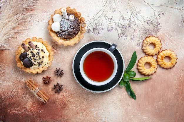 Top vue rapprochée d'un gâteau une tasse de thé assiette de cupcakes biscuits gâteau