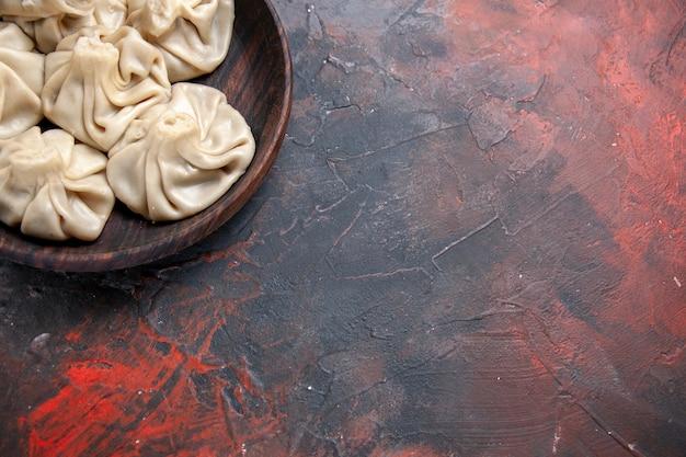Top vue rapprochée khinkali savoureux khinkali dans le bol sur la table rouge-bleu