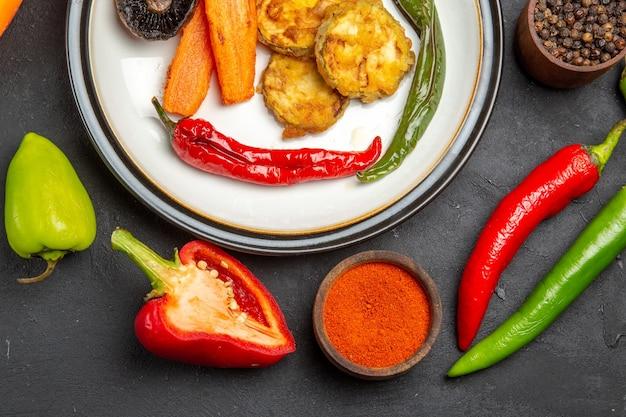 Top vue rapprochée légumes poivrons bols d'épices carottes légumes rôtis