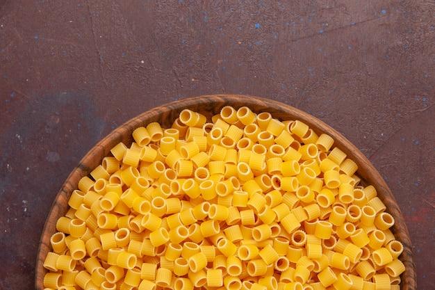 Top vue rapprochée de pâtes italiennes jaunes crues peu formées sur un espace sombre