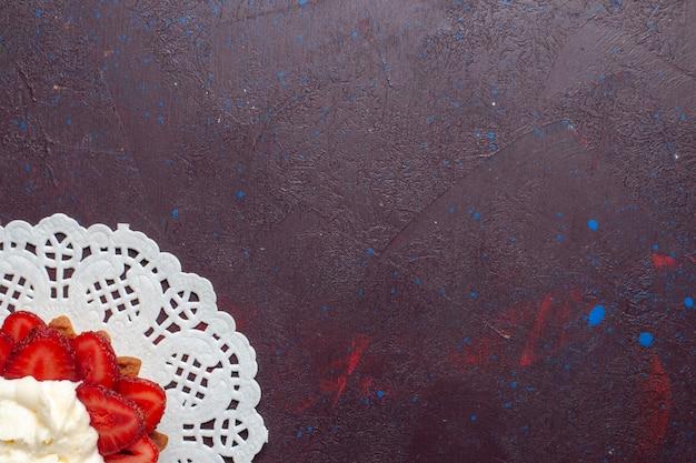 Top vue rapprochée petit gâteau crémeux avec des fruits en tranches sur la surface sombre