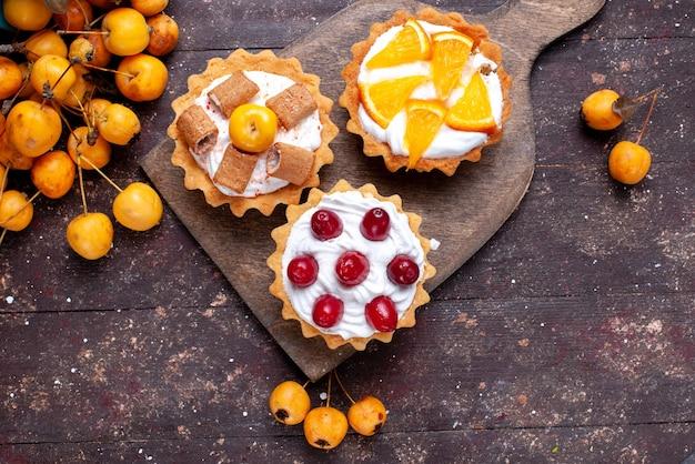 Top vue rapprochée de petits gâteaux délicieux avec de la crème de fruits en tranches et de cerises jaunes fraîches sur brown