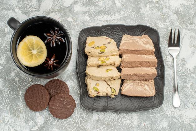 Top vue rapprochée de la plaque de bonbons de graines de tournesol halva fourchette une tasse de biscuits au thé