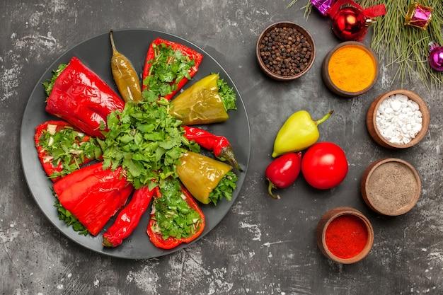 Top vue rapprochée plat poivrons sur la plaque tomates poivrons épices jouets arbre de noël