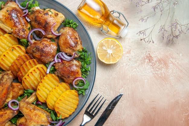 Top vue rapprochée poulet poulet ailes pommes de terre herbes oignons huile citron couteau fourchette