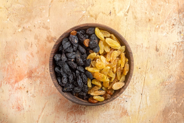 Top vue rapprochée de raisins secs raisins secs verts et noirs dans le bol brun sur la table de crème