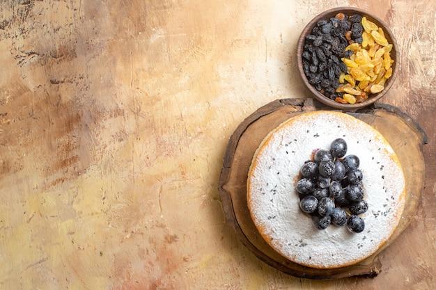 Top vue rapprochée de raisins secs raisins secs verts et noirs dans le bol de gâteau avec des raisins et du sucre en poudre