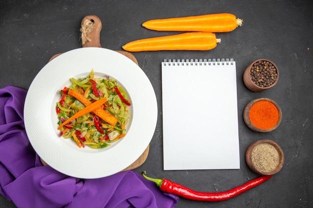 Top vue rapprochée salade de légumes sur la planche à découper épices carottes cahier