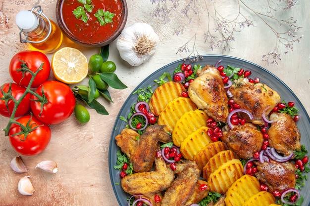 Top vue rapprochée sauce ail assiette de pommes de terre au poulet tomates à l'huile avec pédicelles sauce citron
