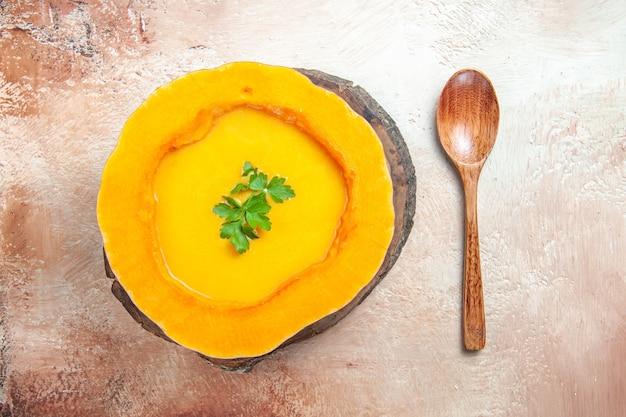 Top vue rapprochée d'une soupe une soupe de potiron sur le plateau à côté de la cuillère