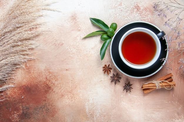 Top vue rapprochée une tasse de thé une tasse de thé bâtons de cannelle agrumes