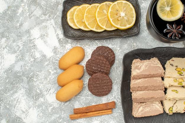 Top vue rapprochée une tasse de thé une tasse de thé biscuits à la cannelle bonbons au citron sur la plaque