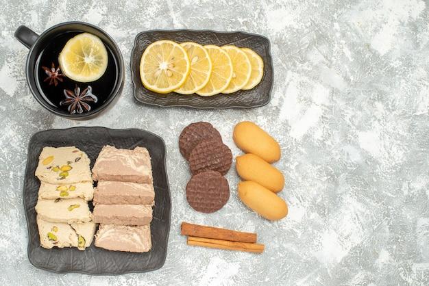 Top vue rapprochée une tasse de thé une tasse de thé cannelle différents biscuits bonbons au citron sur la plaque