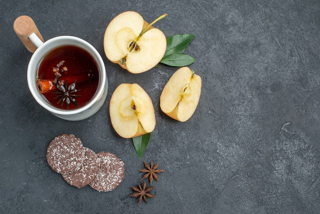 Top vue rapprochée une tasse de thé une tasse de thé avec des tranches de pomme cannelle cookies