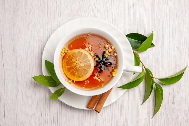 Top vue rapprochée tisane une tasse de tisane avec des bâtons de citron et de cannelle sur la soucoupe blanche et les feuilles de thé