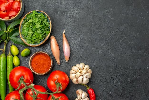 Top vue rapprochée tomates oignons ail épices herbes poivrons tomates sur la table sombre