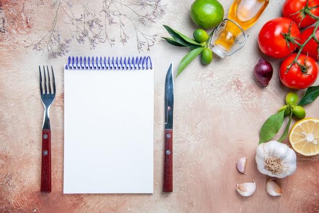 Top vue rapprochée tomates tomates ail bouteille d'huile feuilles de citron fourchette couteau cahier blanc