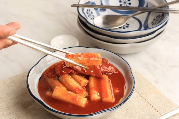 Topokki ou tteokbokki est un gâteau de riz sauté avec des légumes et un gâteau de poisson dans une sauce épicée avec des graines de sésame, une cuisine de rue coréenne célèbre et populaire