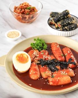 Topokki ou tteokbokki est un gâteau de riz sauté avec des légumes et un gâteau de poisson à la sauce épicée