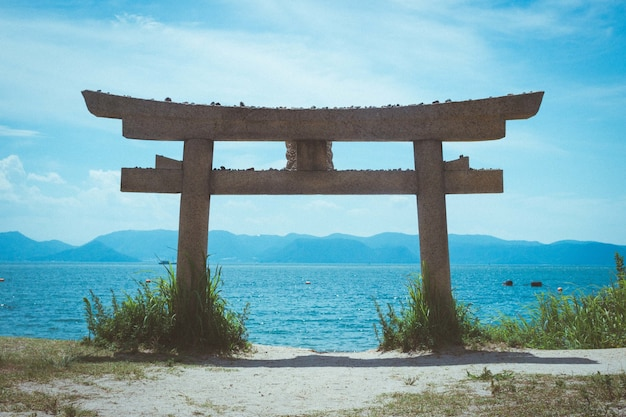 Torii sur une plage de l'île de naoshima sous la lumière du soleil au japon