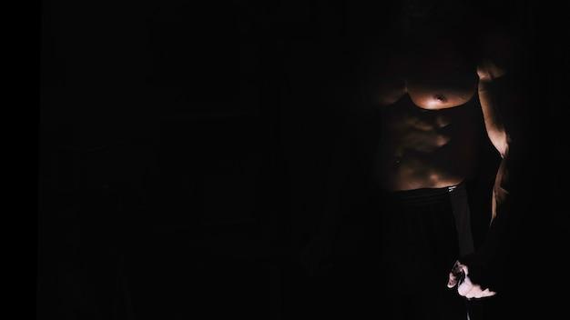 Le torse de l'homme dans l'ombre