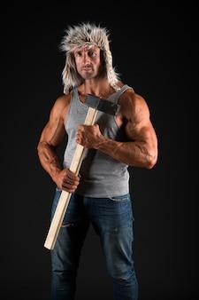 Torse musclé nu sexy de bûcheron de bûcheron. homme brutal et séduisant. équipement de bûcheron de hache. l'homme brutal bûcheron sexy porte une hache. notion masculine. bûcheron érotique. la brutalité est nouvelle sexy.