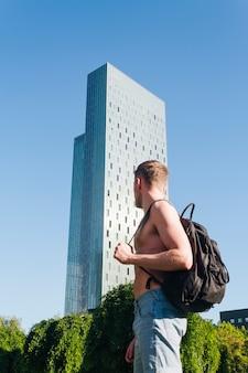 Torse nu jeune homme portant un sac à dos à l'extérieur