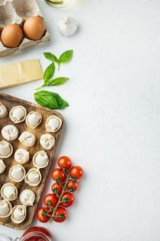 Tortellini italien avec des feuilles de ricotta fraîches et des tomates dans un plateau en bois, sur fond blanc, vue de dessus à plat,
