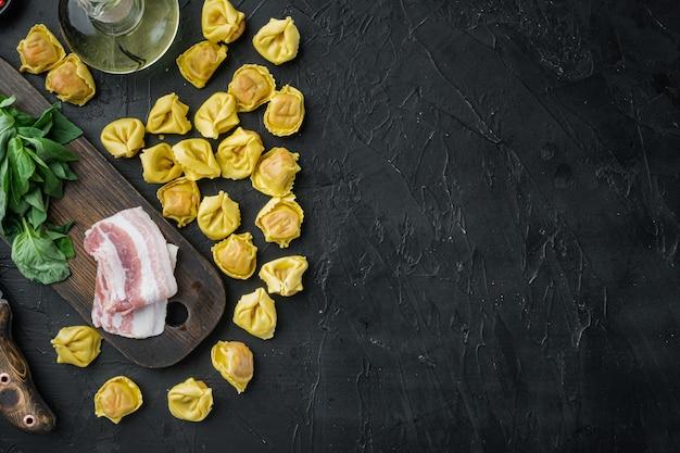 Tortellini maison crue avec du jambon séché, sur une planche à découper en bois, sur table noire, vue de dessus à plat
