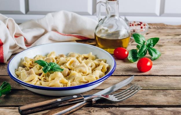 Tortellini avec sauce au fromage, feuilles de basilic dans un bol sur une table en bois rustique.
