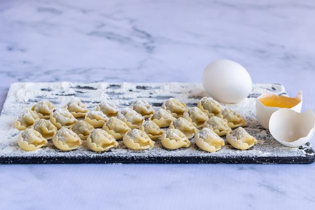 Tortellini saupoudré de farine sur un tableau noir sur marbre