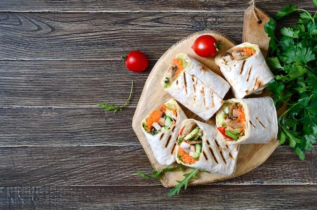 Tortilla fraîche s'enroule avec du poulet, des champignons et des légumes frais sur une planche de bois. burrito mexicain au poulet. apéritif savoureux. plats à base de pain pita. concept d'aliments sains.