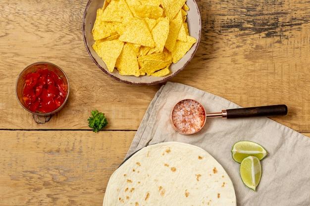Tortilla et nachos près de tomates, sel rose et citron vert