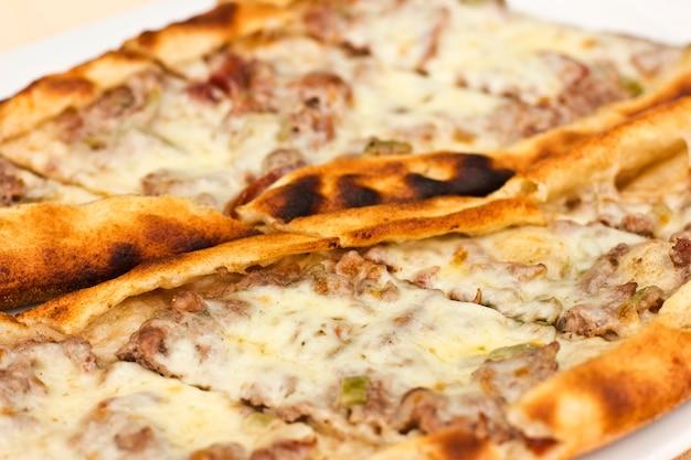 Tortilla pita turque avec des morceaux de viande, du fromage fondu et des tranches de légumes