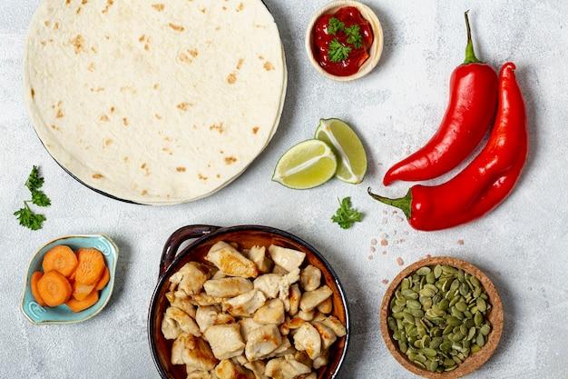 Tortilla et plat de poulet près d'assortiment de légumes