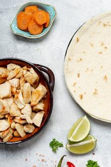 Tortilla et plat de poulet près de carottes en tranches et citron vert