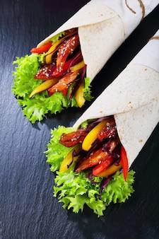Tortilla roulée avec salade de chou rouge, lanières de poivrons doux et viande de poulet frit