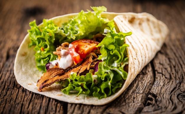 Tortilla avec viande, tomate, salade, oignon et crème.