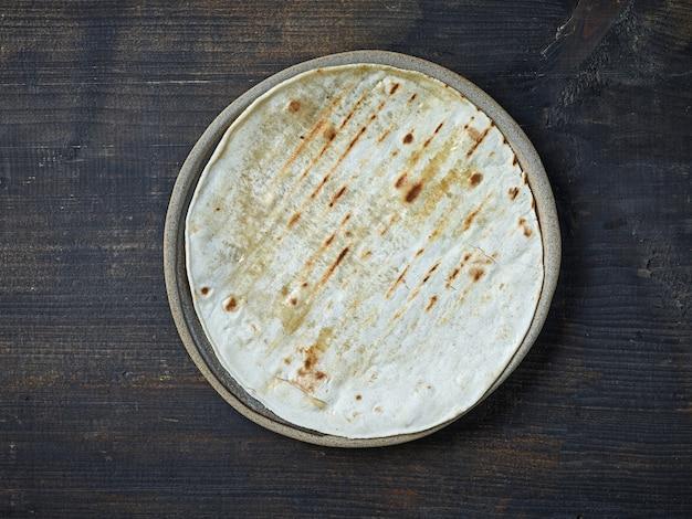 Tortilla vide sur plaque en céramique sur table de cuisine en bois noir, vue de dessus