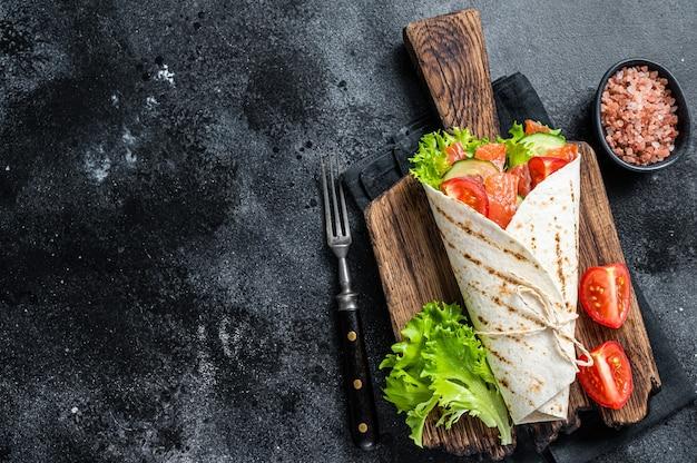 Tortilla wrap roulé au saumon avec salade, légumes. fond noir. vue de dessus. espace de copie.